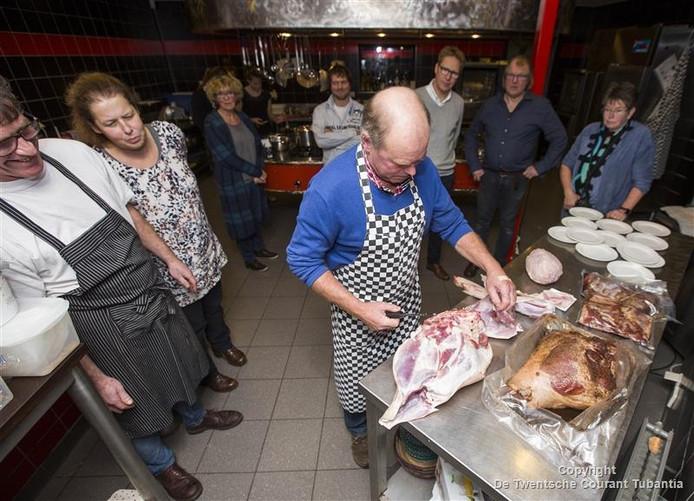 Slechts een handvol gasten kijkt toe hoe Tonny Bossink op de ondernemersdag een varken uitbeent.