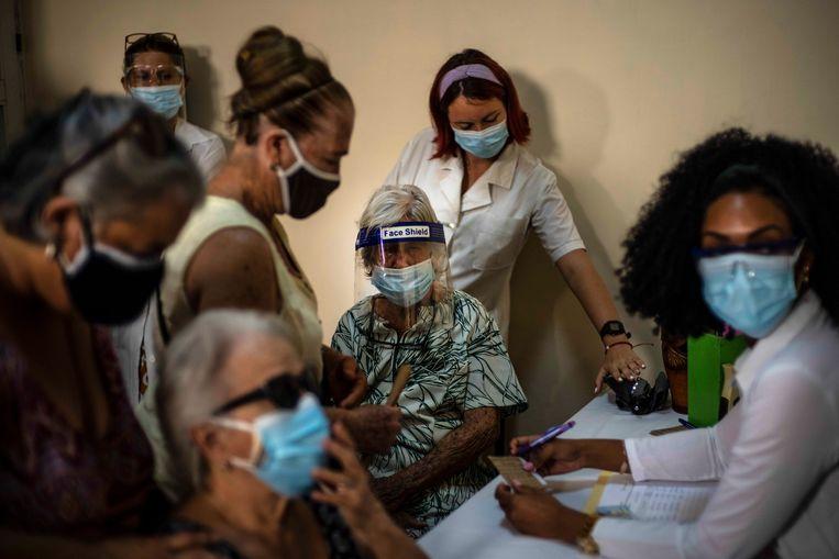 Cubaanse vrouwen in Havana maken een afspraak voor een vaccinatie tegen corona.  Beeld AP