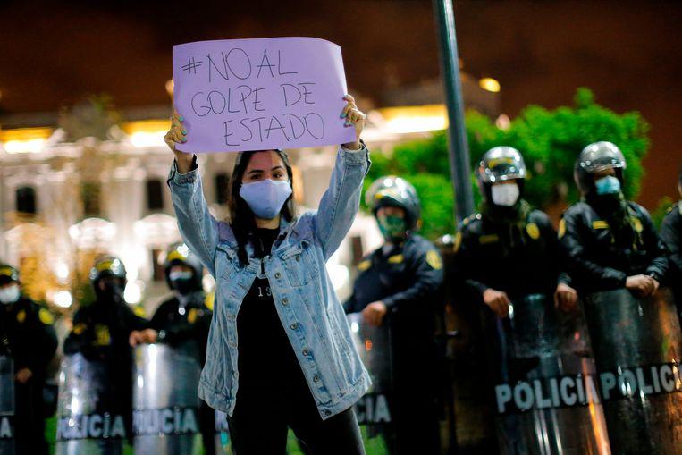 Een aanhanger van president Vizcarra houdt een blad omhoog met de tekst 'nee tegen de staatsgreep.' Beeld AFP