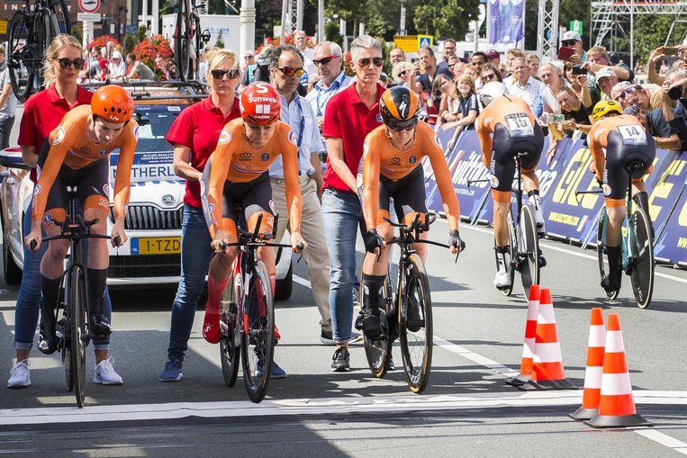 Riejanne Markus, Floortje Mackaij en Amy Pieters (van links naar rechts) gaan van start als Bauke Mollema en Koen Bouwman (rechts) over de finish komen tijdens de gemengde ploegentijdrit tijdens de EK wielrennen.  Beeld ANP