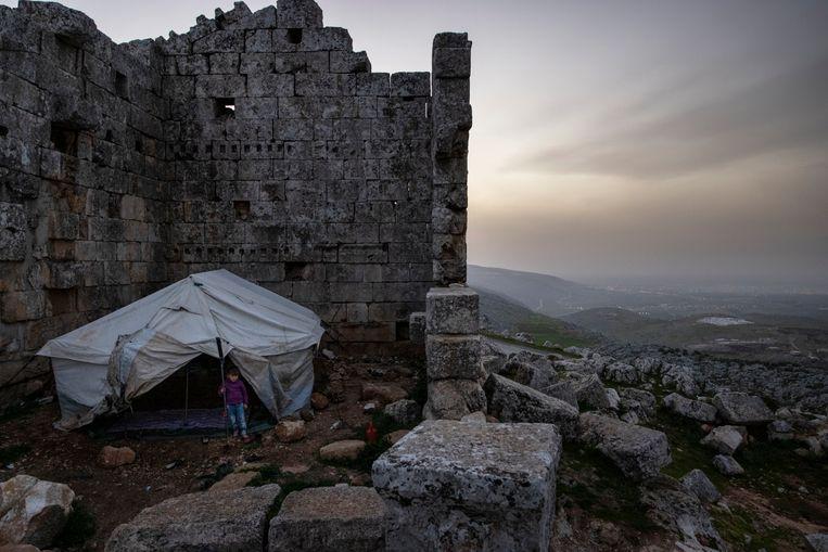 De ruïnes beschermen vluchtelingen nog enigszins tegen wind en regen. Beeld NYT/IVOR PRICKETT