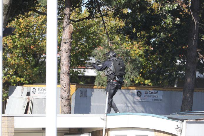 Een lid van het antiterreurteam houdt de man onder schot.