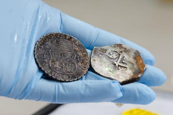 Twee zilveren munten uit het wrak, een met een pers geslagen pilaardollar en een Spaanse mat die beiden evenveel waard zijn, 8 realen. Met de oudere Spaanse mat kon echter meer gesjoemeld worden door er onopvallend zilver vanaf te snoeien.
