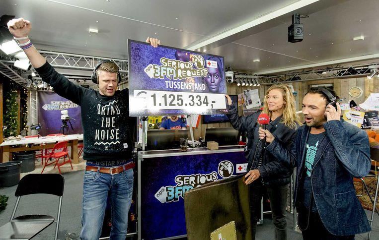 Sophie Hilbrand (midden) laat de tussenstand van 1.125.334 euro zien aan dj's Coen Swijnenberg (links) en Gerard Ekdom). Beeld anp
