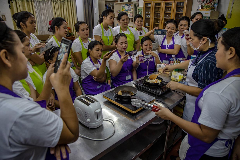 Filipijnse vrouwen leren tijdens de verplichte cursus huishoudelijk werk koken, schoonmaken, zelfverdediging en stressmanagement.  Beeld Ezra Acayan