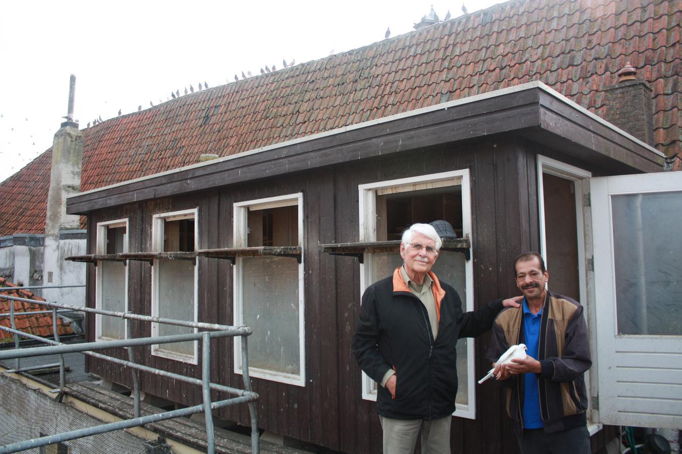 Jan Burger en verzorger Hamid Bhayaje bij de duiventil op het oude Livera-gebouw.