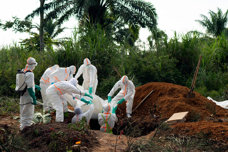 Een slachtoffer van ebola wordt begraven in Beni, Congo. David Quammen: 'Ebola is dodelijker, maar corona is een betere wereldreiziger.'  Beeld AP