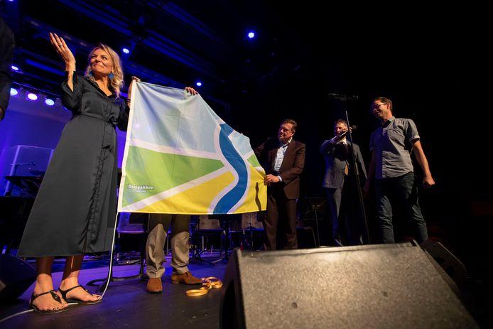 Organisator Barbara Jansen (l) onthult de Sallandse vlag terwijl ontwerper Erik Dijk (helemaal rechts) toelichting geeft op het ontwerp.