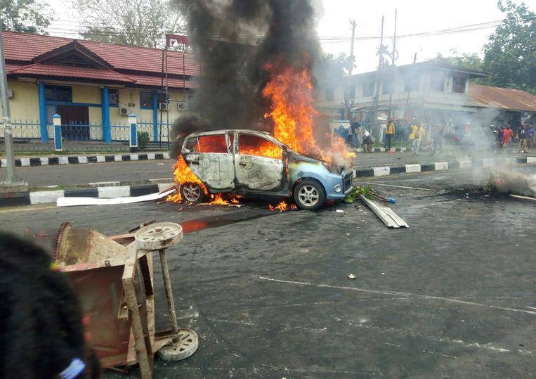 Een auto wordt maandag in brand gestoken tijdens protesten in Manokwari, de hoofdstad van de provincie West-Papoea. Beeld null