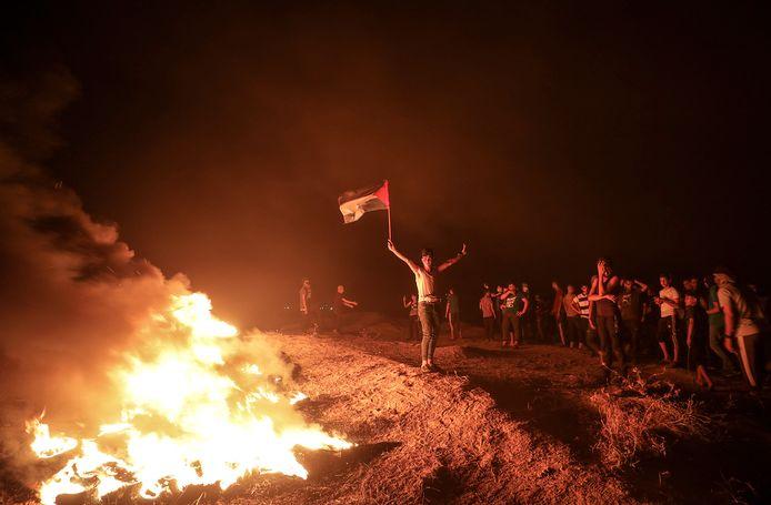Demonstranten zwaaien met de Palestijnse vlag tijdens een protest aan de grens tussen de Gazastrook en Israël.