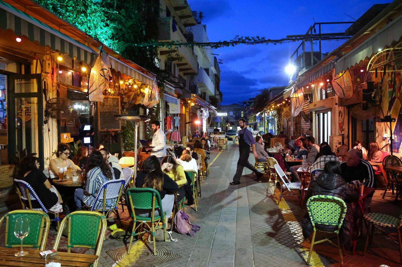 Mensen op terrassen in Tel Aviv. Zondag gingen de restaurants en cafés in Israël weer open, maar alleen voor mensen die kunnen aantonen dat ze zijn gevaccineerd, of zijn hersteld van het coronavirus.  Beeld AFP
