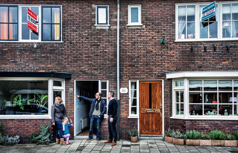 Stroomstraat 27 in Utrecht trekt veel kijkvolk. De makelaar (rechts) in gesprek met potentiële kopers.  Beeld Raymond Rutting / de Volkskrant