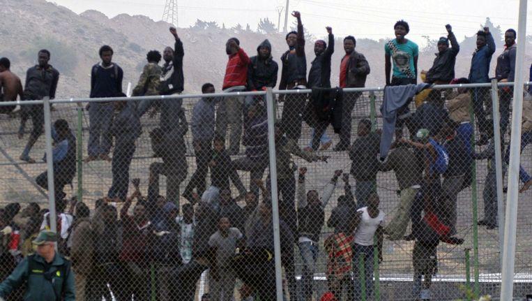 Tientallen immigranten klimmen over het hek bij de grens tussen Marokko en en de stad Mellila in Spanje, mei 2014. Beeld null