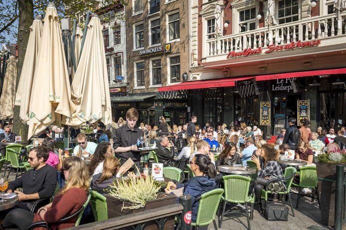 Het beeld van volle terrassen, zoals hier op het Leidseplein in Amsterdam (archieffoto), zou Nederlanders weer perspectief geven.