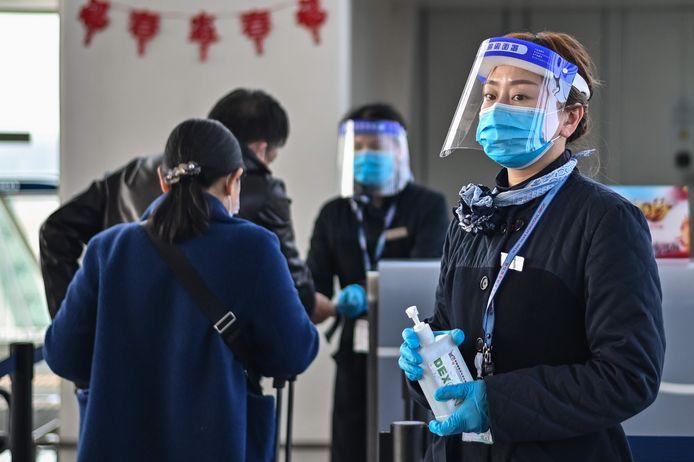 Een medewerkster van de luchthaven van Wuhan staat klaar om de handen van passagiers te ontsmetten met alcoholgel.