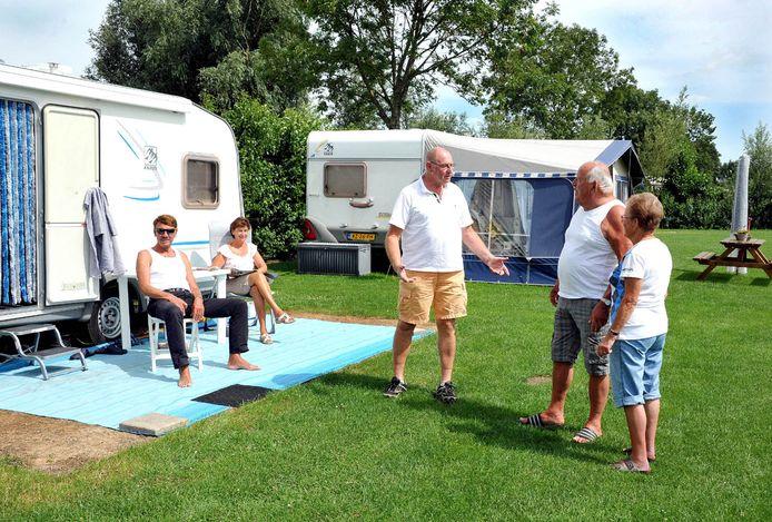 Juli 2011: Wim van den Berg (midden) op de camping De Victorie in gesprek met enkele gasten.