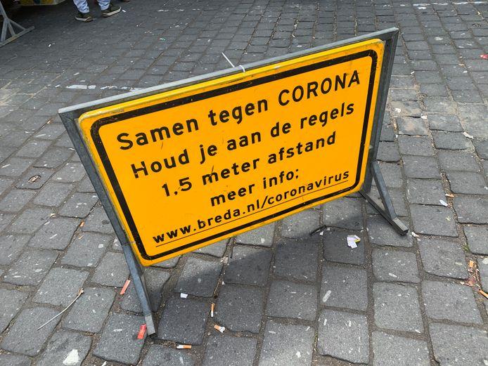Op de Grote Markt in Breda staan borden die het publiek waarschuwen om de coronarichtlijnen in acht te nemen.