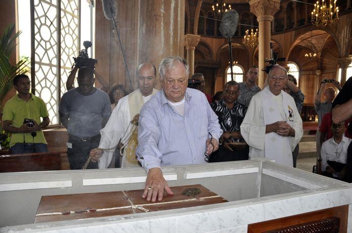 Jacques de Leeuw raakt de kist aan met de stoffelijke resten van Peerke Donders. Rechts van hem bisschop Wim Bekker. foto: Paul Spapens