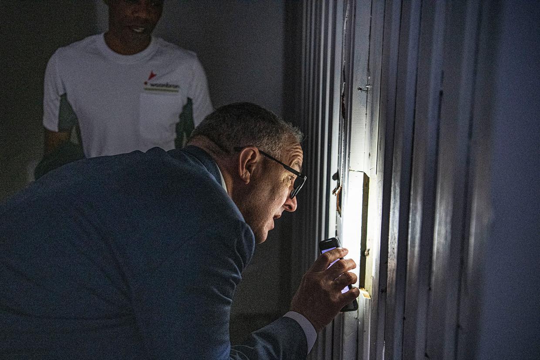 Met het lampje op zijn telefoon tuurt Aboutaleb in een inmiddels afgesloten kelderbox waar tot voor kort iemand sliep. Beeld Guus Dubbelman / de Volkskrant
