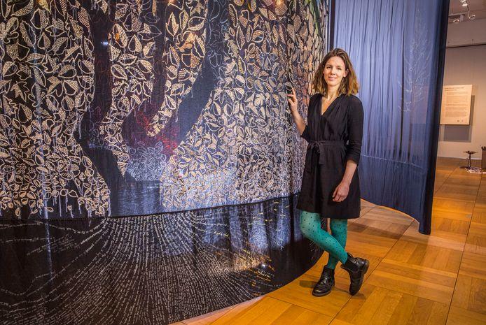 Kunstenares Sara Vrugt bij een gedeelte van haar samen met vrijwilligers geborduurde bos.