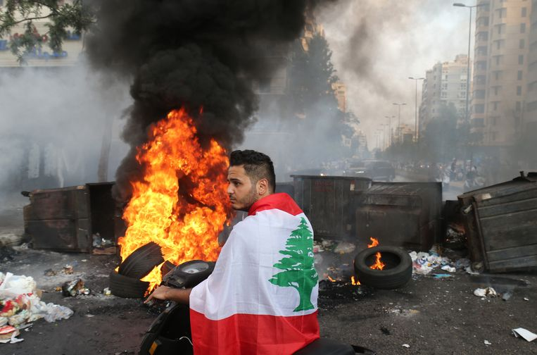 Een man gehuld in de Libanese vlag om, bij een wegblokkade van brandende vaten en autobanden.  Beeld EPA