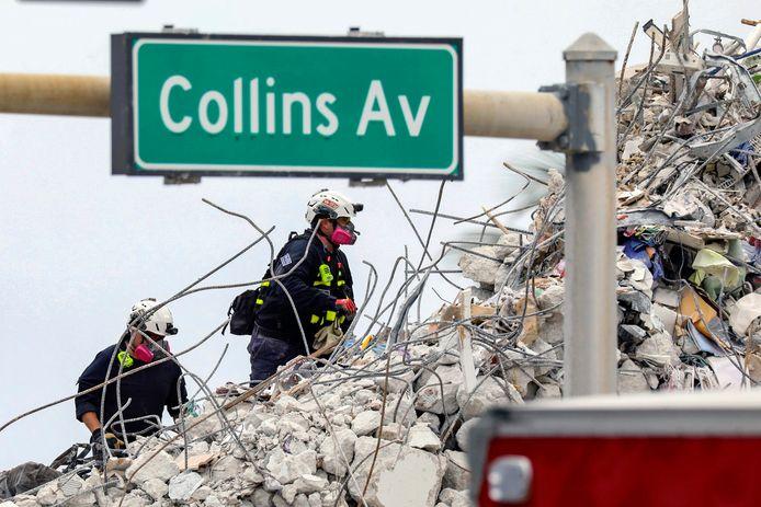 Reddingswerkers op de puinhopen van het ingestorte flatgebouw.