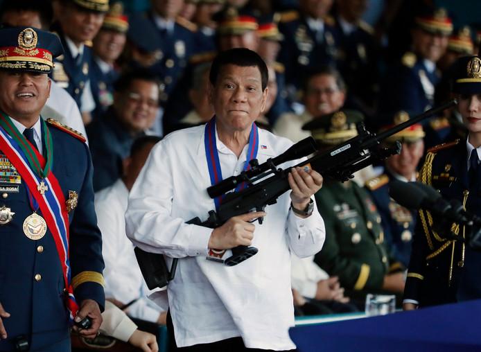 Rodrigo Duterte avec un fusil sniper dans les bras lors d'un meeting.