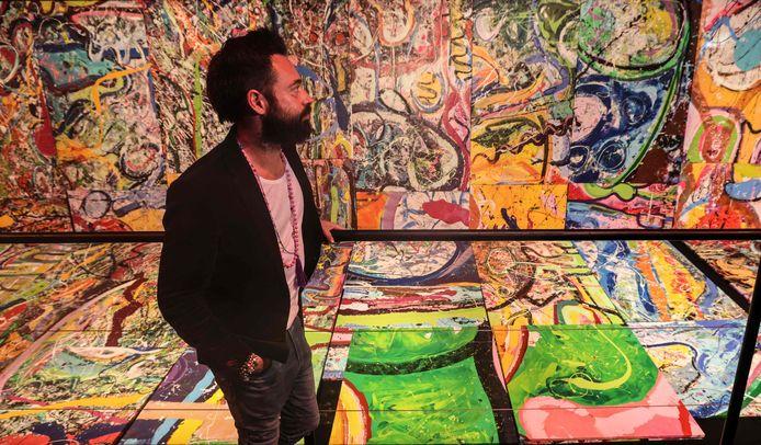 Sacha Jafri staat voor een klein stukje van het enorme schilderij.
