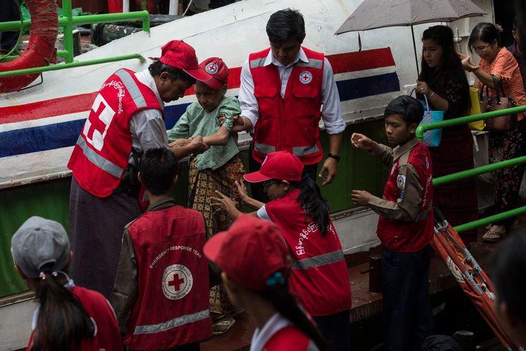 Medewerkers van het Rode Kruis helpen een oudere vrouw die op de vlucht geslagen is voor het geweld in haar regio. Beeld afp