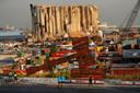 Inwoners van Beiroet bij een symbolisch monument voor gerechtigheid voor de slachtoffers - ruim 200 doden en 6500 gewonden - van de explosie op 4 augustus 2020 in de haven. Op de achtergrond de zwaar beschadigde graansilo's.