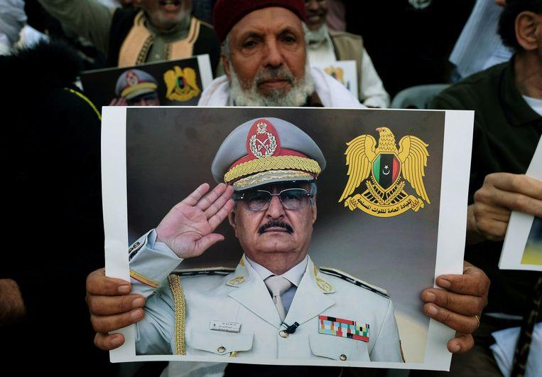 Een man houdt een foto van Khalifa Haftar omhoog tijdens een demonstratie in Tripoli. Beeld REUTERS