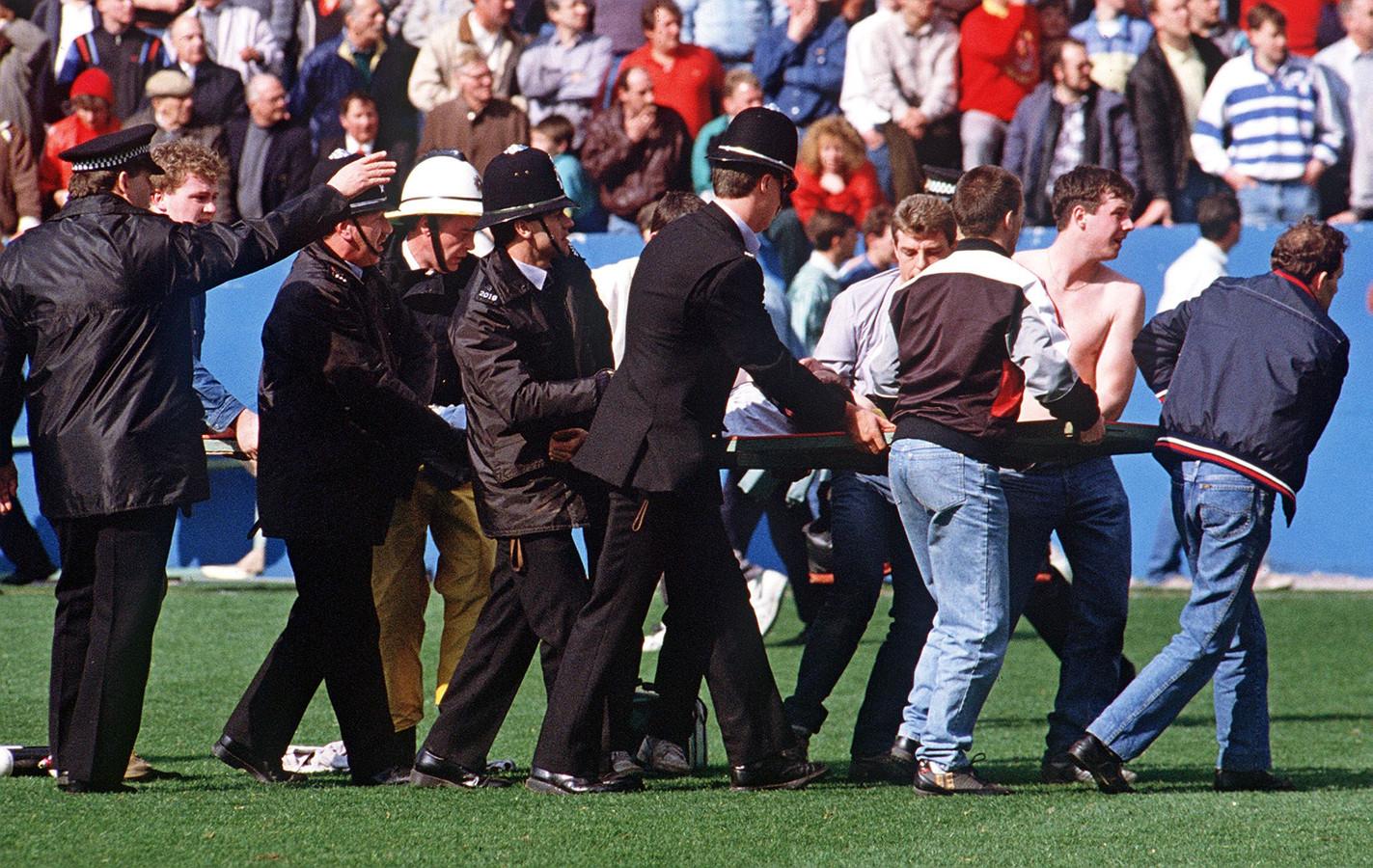 15 april 1989: supporters en agenten dragen op een reclamebord een gewonde supporter weg. 96 mensen overleefden het gedrum in het stadion niet.