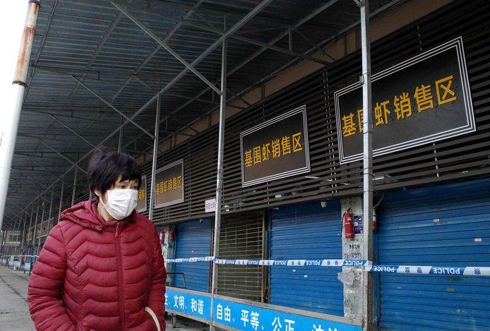 Een Chinese vrouw loopt met mondbescherming tegen mogelijke besmetting bij de gesloten vismarkt van Wuhan, waarschijnlijk de bron van het mysterieuze longvirus.
