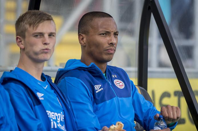 Eloy Room (rechts) op de bank bij PSV, samen met Albert Gudmundsson. Beide spelers staan vanavond waarschijnlijk in de basis tegen NEC.