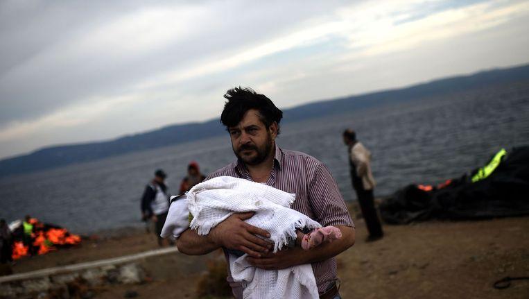 Een Syrische vluchteling loopt met zijn baby het Griekse eiland Lesbos op, na een gevaarlijke reis vanuit Turkije. Beeld afp