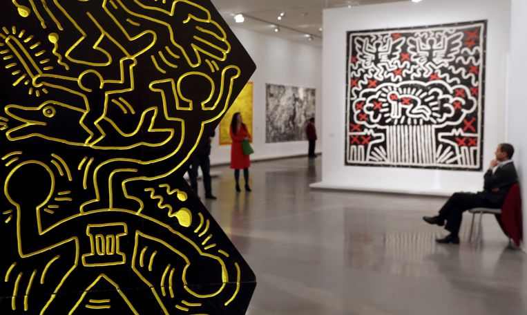 A guard sits near a creation, 'Untitled 1982' (R) by the late American artist Keith Haring (1958-1990) during his retrospective exhibition at the Musee d'Art Moderne (Modern Art Museum) in Paris April 18, 2013. The exhibition