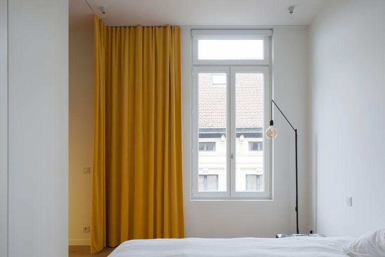 Geelkoperen gordijnen van zacht fluweel brengen gezelligheid in de sober ingerichte slaapkamer.  Beeld Johnny Umans