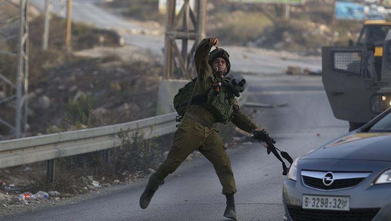 Een Israëlische soldaat gooit een geluidsgranaat naar Palestijnse demonstranten. Beeld REUTERS