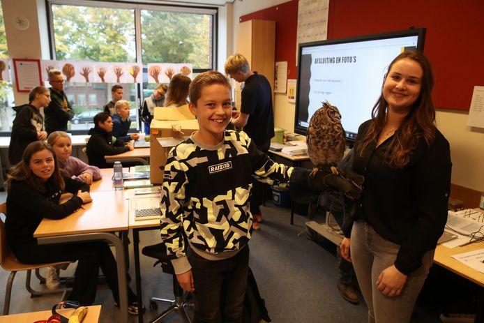 Laura de Vries en (op de achtergrond) Kasper Gielen gaven woensdag op hun oude school de Kastanjelaar in Milheeze een roofvogelpresentatie.  Leerling Jens Teluy mocht een Oehoe even op zijn hand nemen.