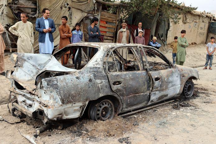 Des habitants voient un véhicule endommagé par une attaque à la roquette à Kaboul, Afghanistan, lundi 30 août 2021.