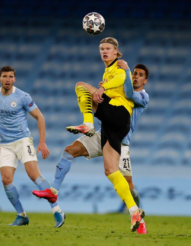 Joao Cancelo van Manchester City probeert te voorkomen dat Erling Braut Haaland de bal aanneemt. Beeld REUTERS