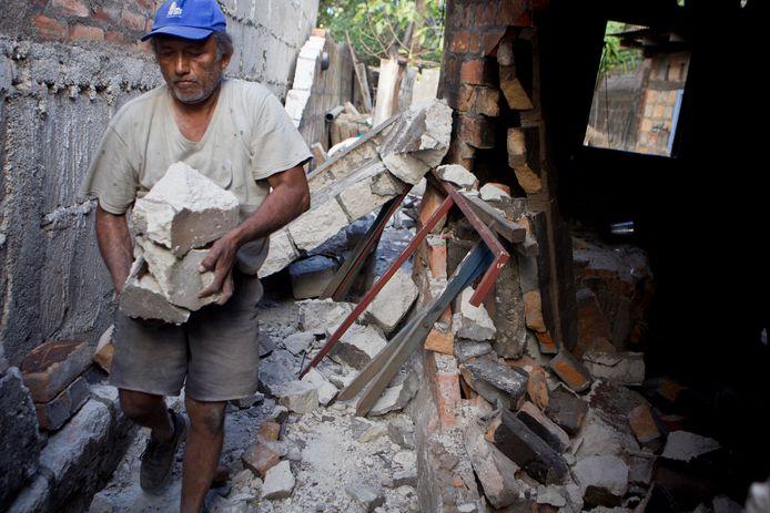 Archiefbeeld 11 april 2014: een man probeert enkele brokstukken op te ruimen na een aardbeving in het Centraal-Amerikaanse land Nicaragua.