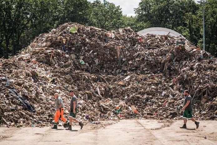 Des hommes passent devant une pile de déchets au centre de gestion des déchets, une installation de stockage provisoire pour les déchets encombrants provenant des régions inondées de la vallée de l'Ahr, à Niederzissen, en Rhénanie-du-Nord-Westphalie, dans l'ouest de l'Allemagne, le 30 juillet 2021.