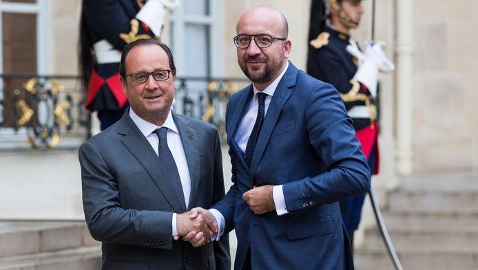 Premier Michel schudt de hand van president Hollande bij zijn aankomst vanmorgen op het Elysée.