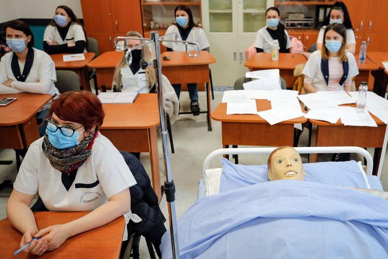 In Roemenië zijn de scholen weer open, na een lockdown vanwege het coronavirus. In dit klaslokaal in Boekarest worden verpleegkundigen opgeleid, met hulp van een oefenpop. Beeld AP