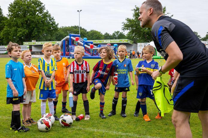 Begeleider Bram legt het voetbal kat en muis spel uit aan de spelertjes van Manchester City en Newcastle United tijdens de Voetbaldag bij VV Baardwijk.