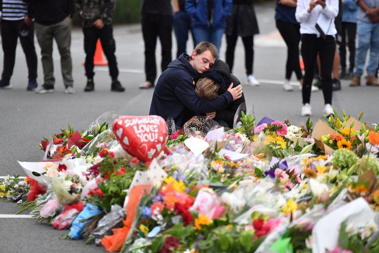 Inwoners rouwen bij een bloemenzee nabij de Al Noor Masjid-moskee in Christchurch, Nieuw-Zeeland, waar bij een terreuraanslag vrijdag zeker 49 mensen om het leven kwamen. Beeld EPA