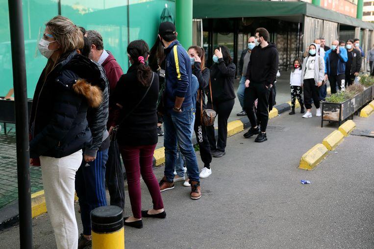 Libanezen doen nog snel hun laatste boodschappen, voordat ook de supermarkten de deuren sluiten.  Beeld AP