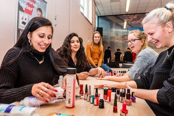 Studenten van mboRijnland zamelen geld in om een school op te knappen in Bosnië. Vlnr Rabina en Samira lakken voor 2,50 euro de nagels van Jennifer, Marinde en Senna.