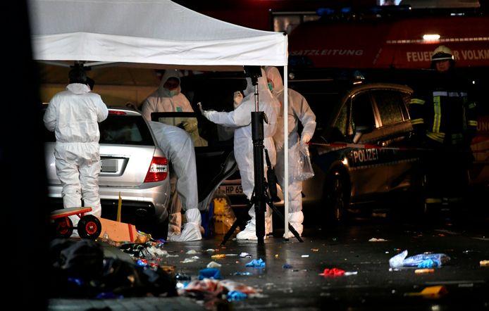 Forensische speurders onderzoeken de auto van de verdachte op de plaats delict.